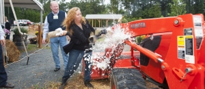 Robin Taylor, farm manager, christens a tractor