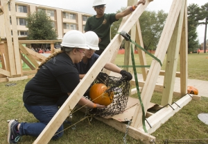 Engineering students load a pumpkin into their team's trebuchet