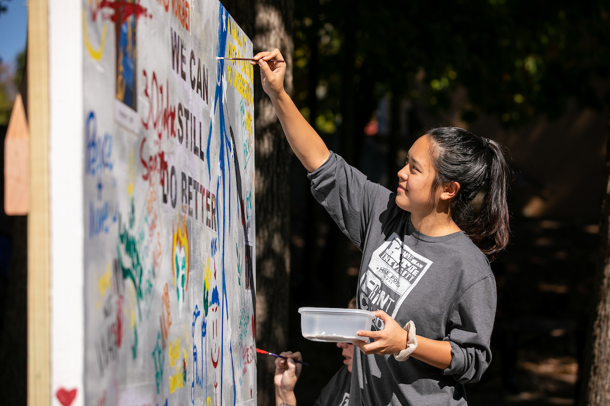 A KSU student paints a replica piece of the Berlin Wall