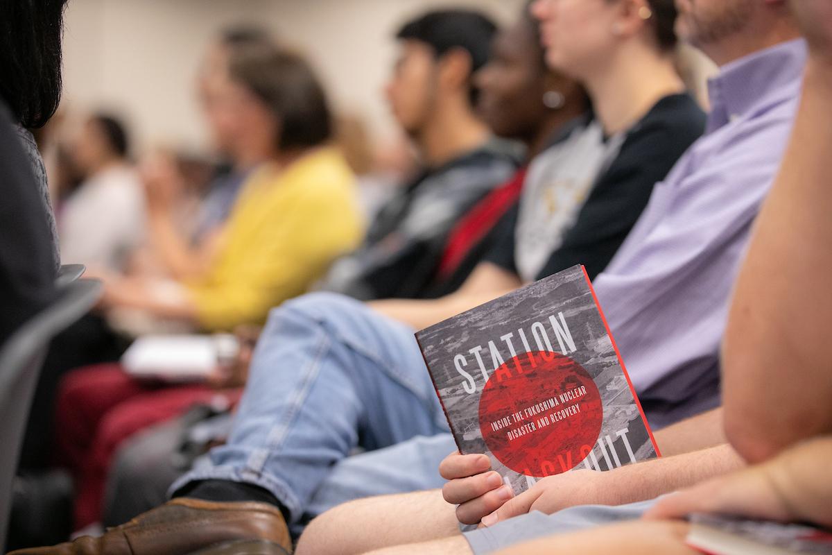 Students hold a copy of KSU alum Charles Castro's book, Station Blackout